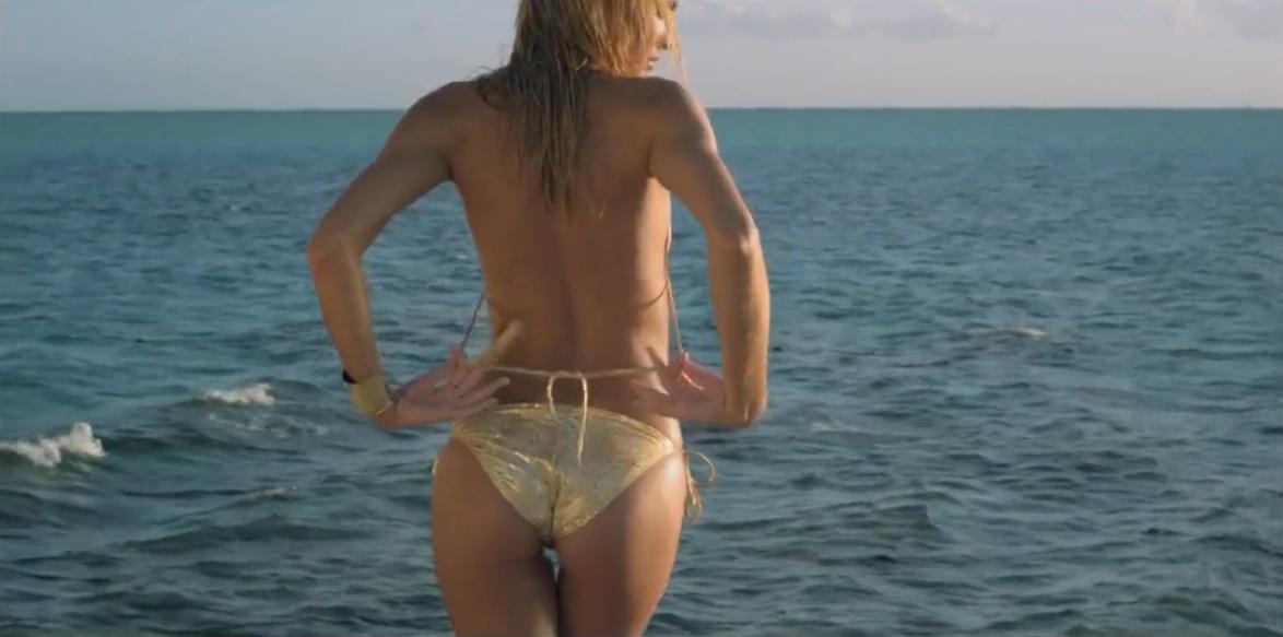 sexy Blondine in goldenem Bikini am Strand