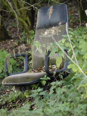 alter zerschlissener Schreibtischstuhl im Wald