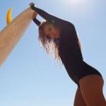 blonde Surferin stemmt Surfbrett