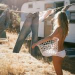 Blondine in Höschen hängt Wäsche auf